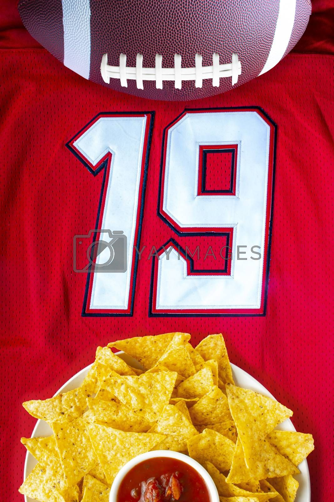 An American football with organic nacho chips and mild salsa on a white red football jersey with the 19 number