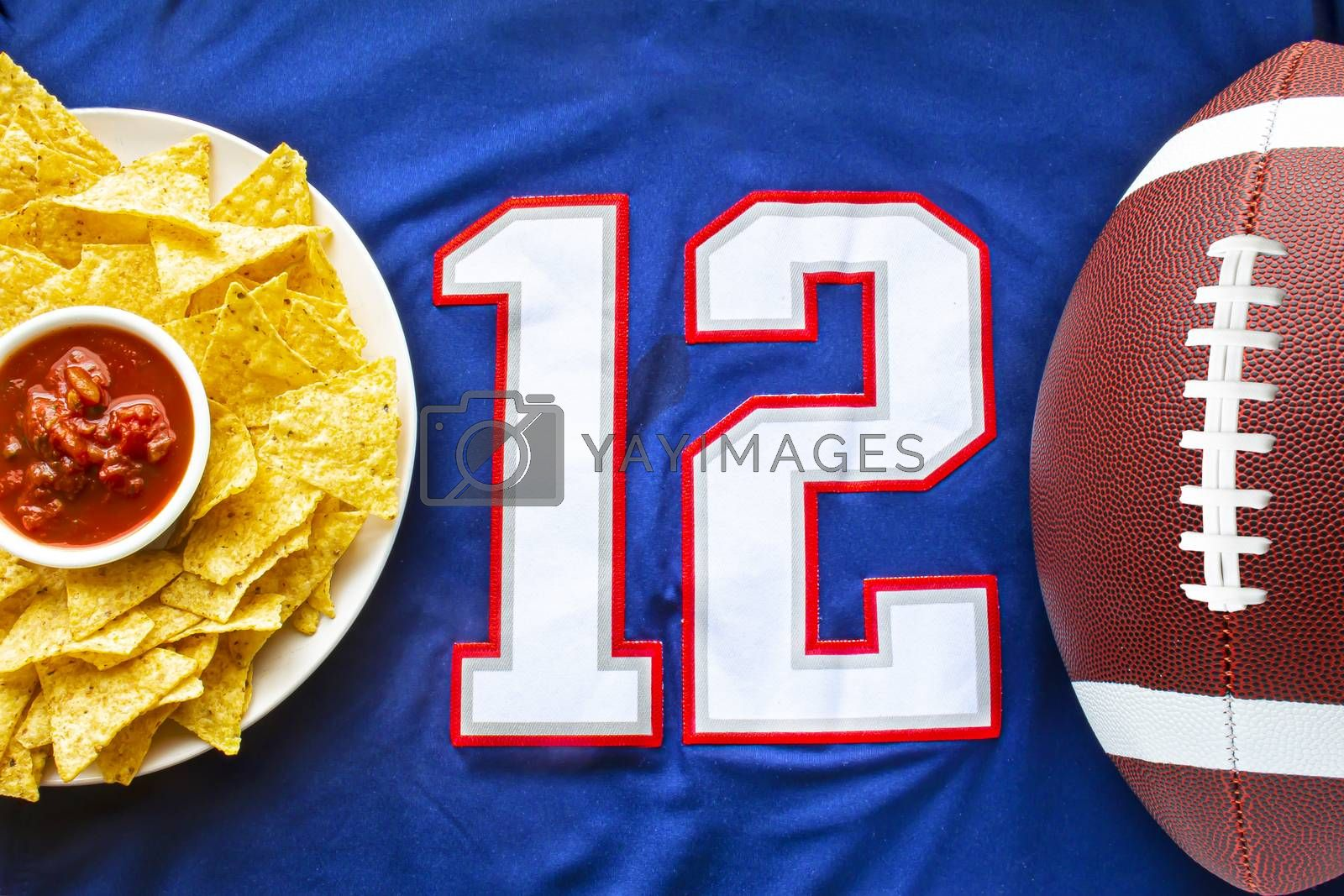 An American football with organic nacho chips and mild salsa on a white blue football jersey with the 12 number on horizontal view