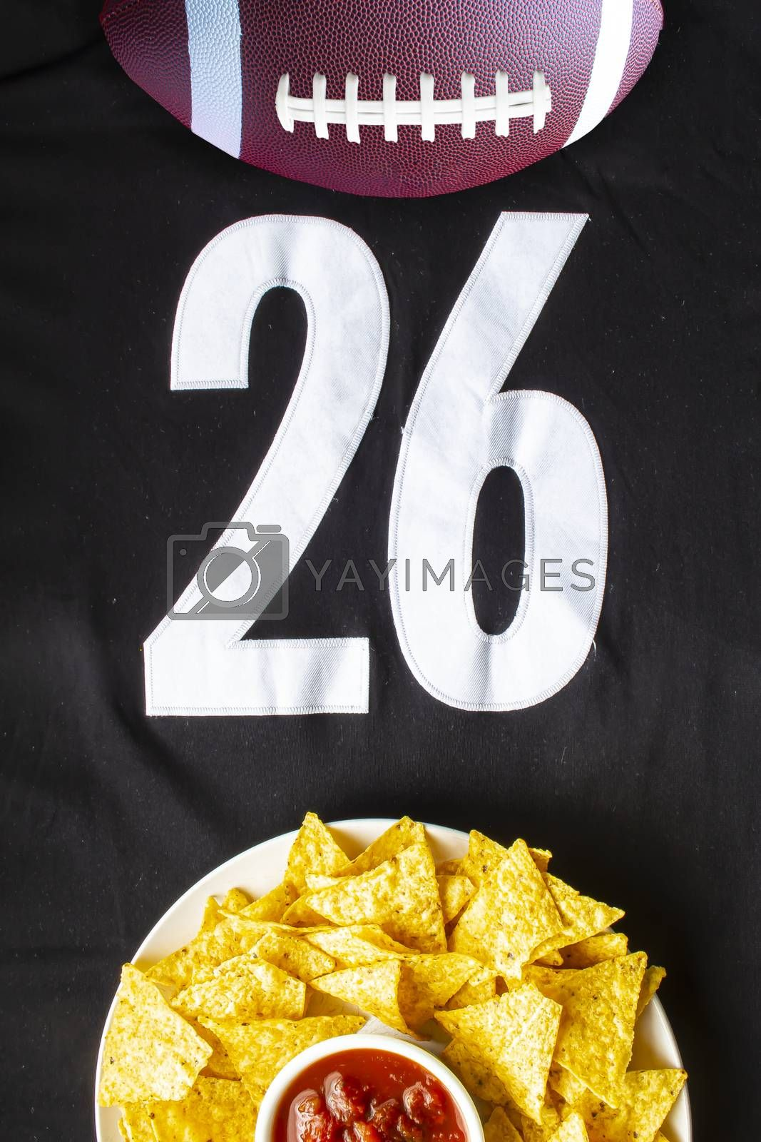 An American football with organic nacho chips and mild salsa on a white black football jersey with the 26 number on vertical view