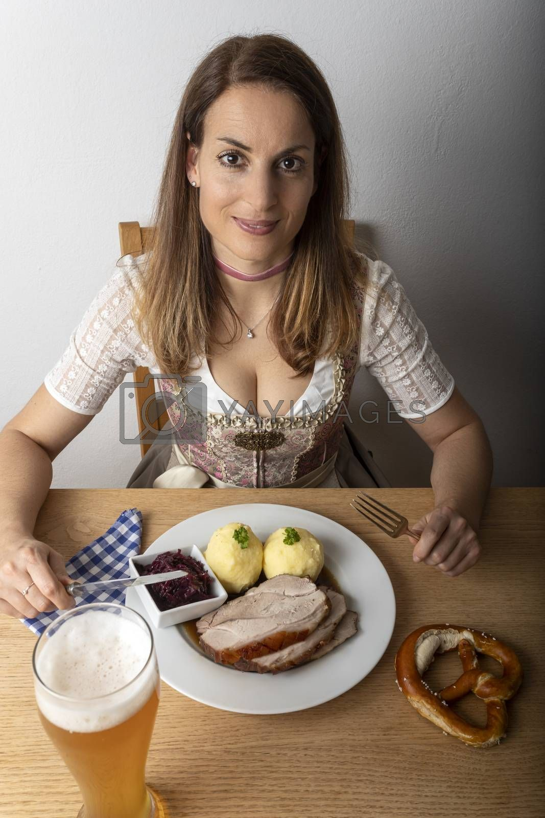 woman with a dirndl eating roasted pork by bernjuer