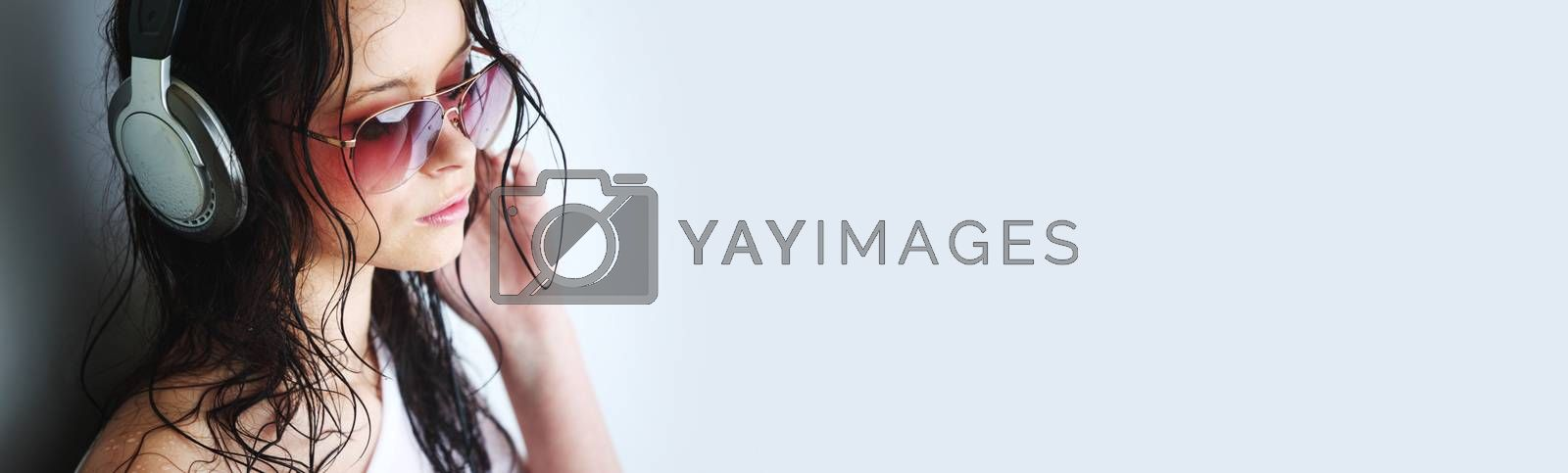 Young woman listening to music on headphones enjoying a dance. Closeup portrait of girl on light background with copy space