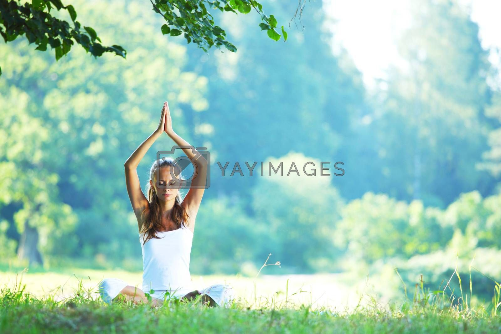 Yoga woman in white on green park grass in lotus asana pose