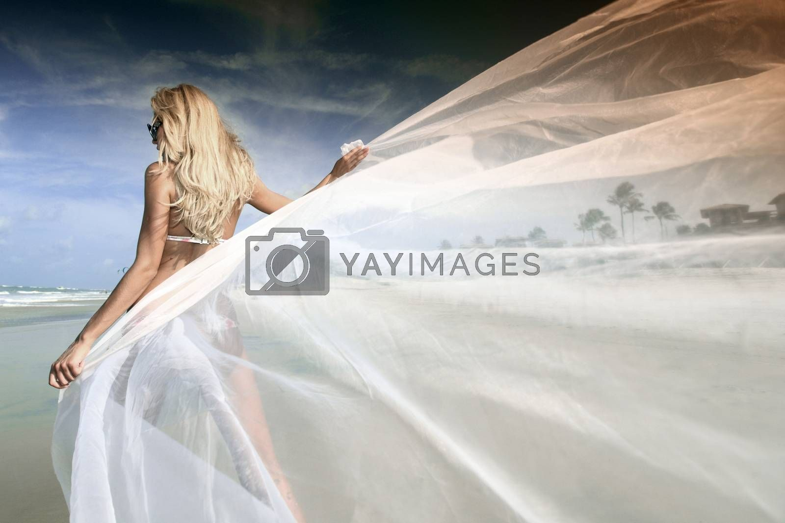 Young woman holding white fabric on the ocean beach, bride vacation on ocean coast