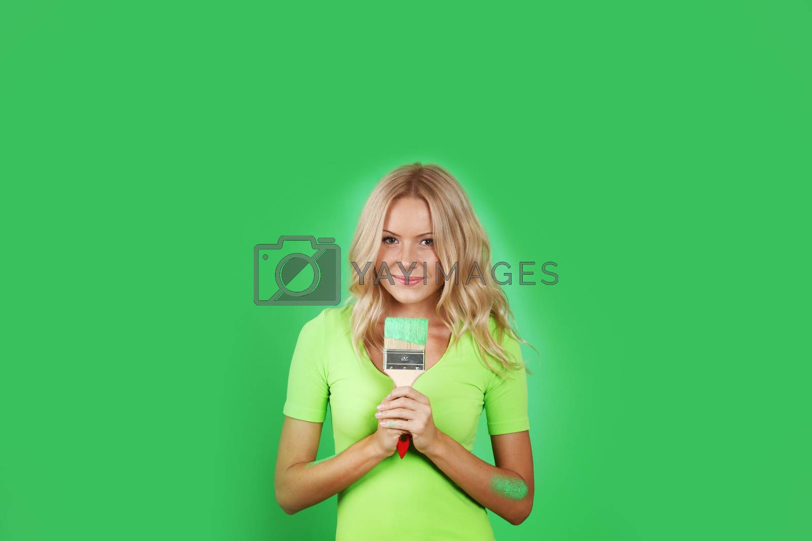 Portrait of cute smiling young woman painting green wall with paint brush and renovating home copy space for text