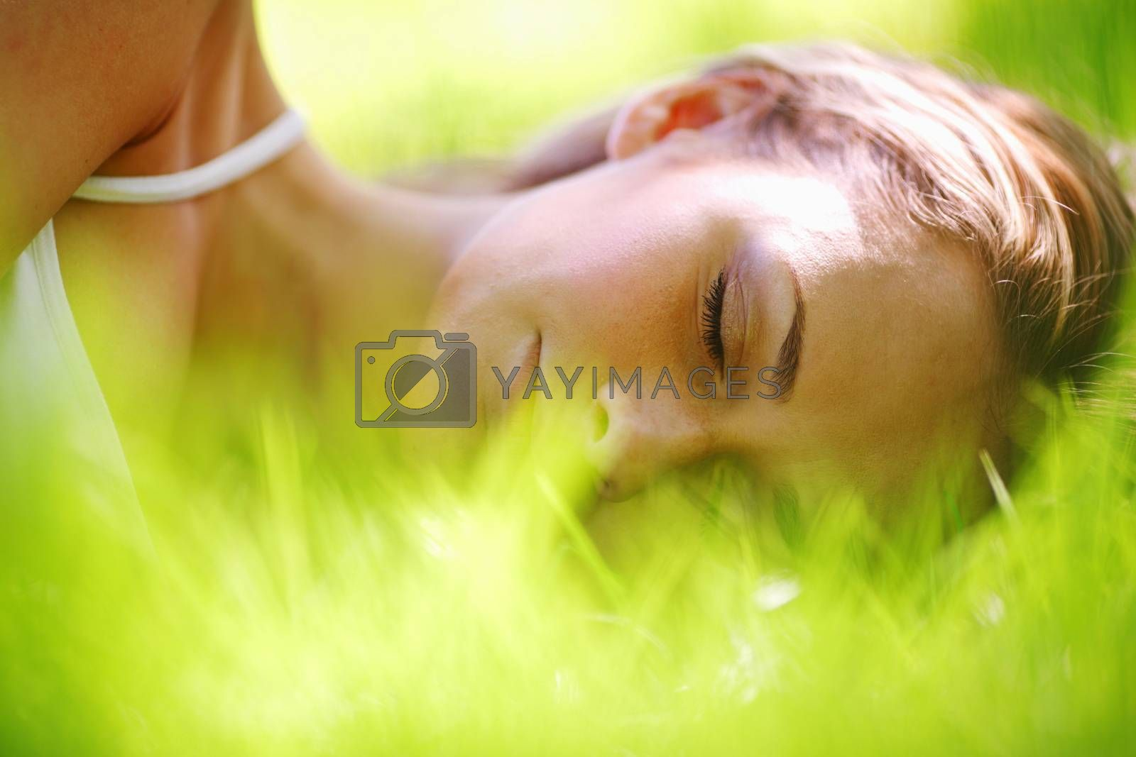 Beautiful young woman sleep on green spring grass