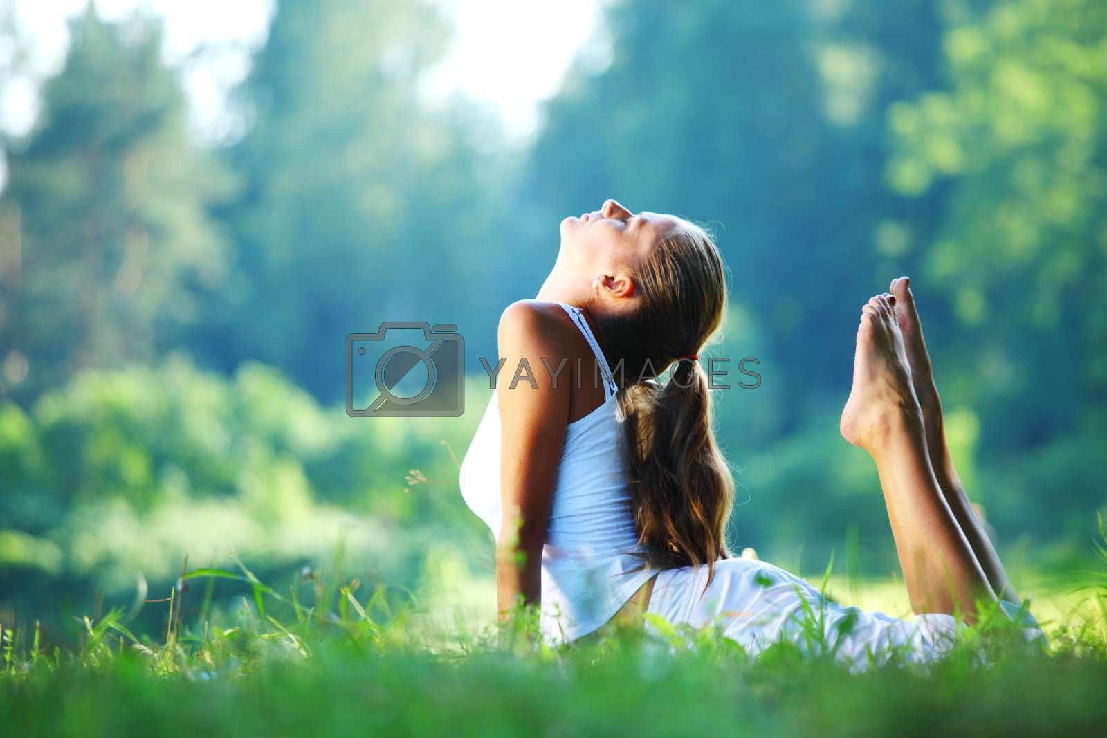 Yoga woman in white on green park grass in cobra asana pose