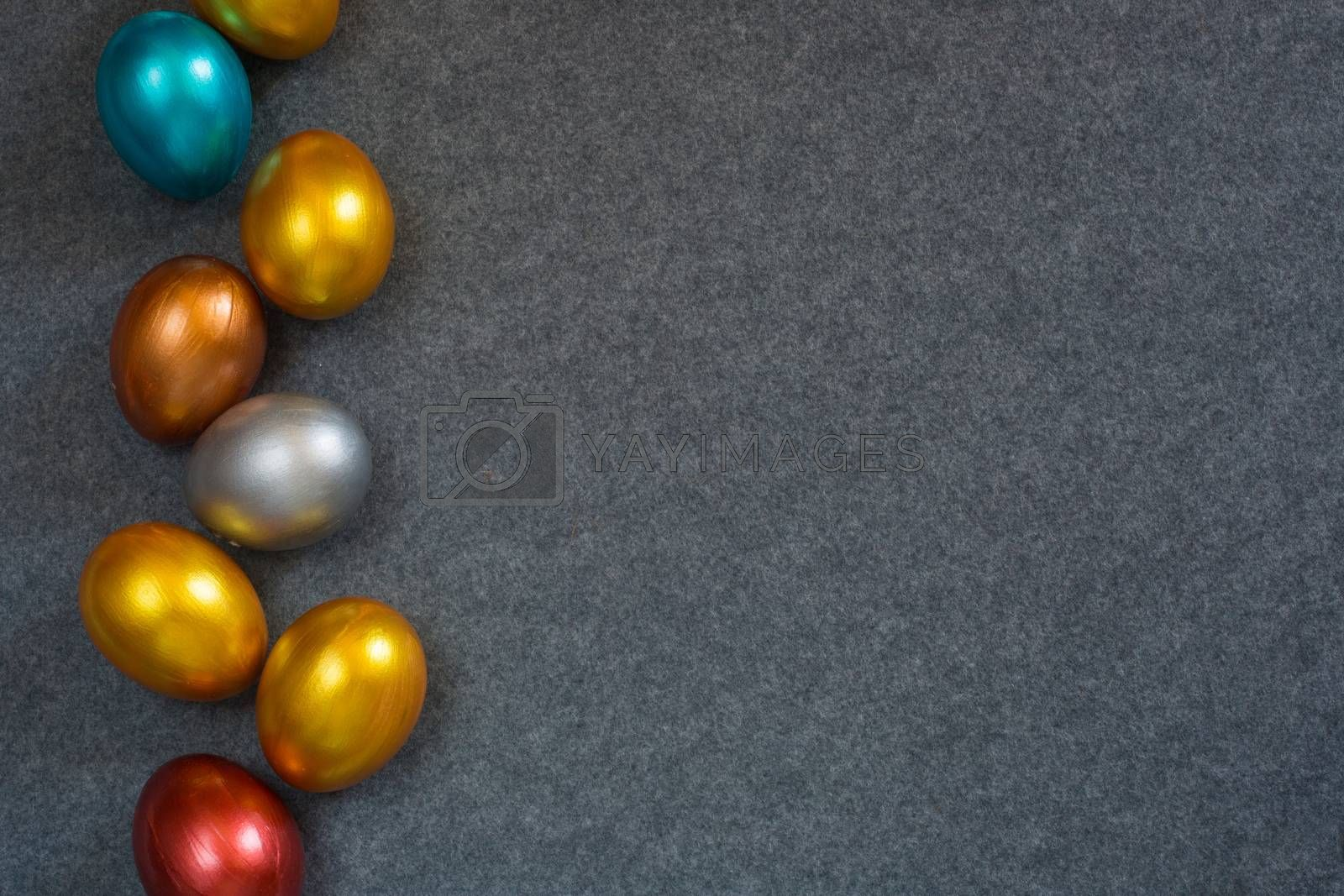 Elegant fashion background with border frame of decorative color metallic Easter eggs on textile background, copy space for text. Top view flat lay