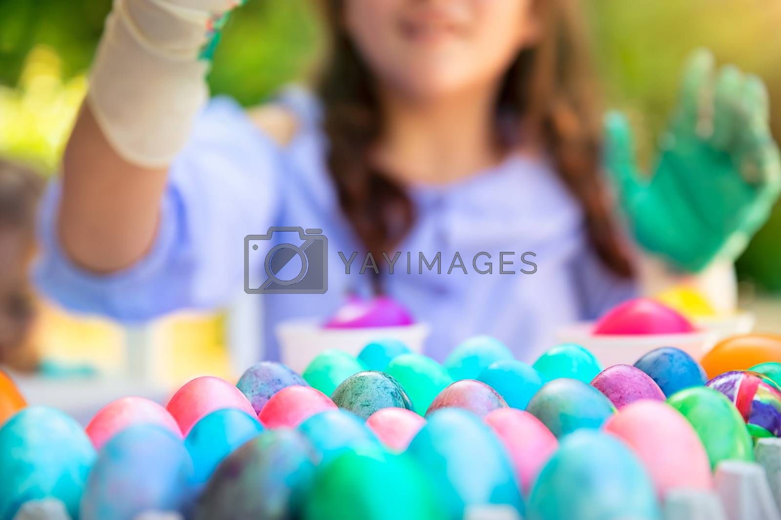 Closeup photo of a many colorful Easter eggs, little girl with pleasure decorates traditional Easter symbol, springtime fun, happy religious holiday