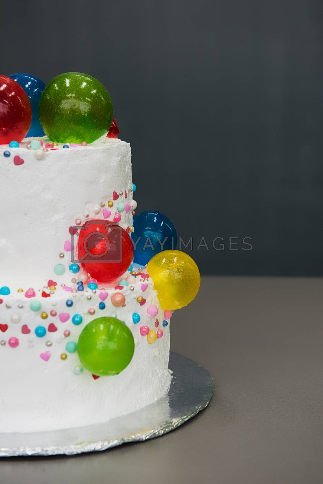 Wedding cake with caramel balloons on grey background