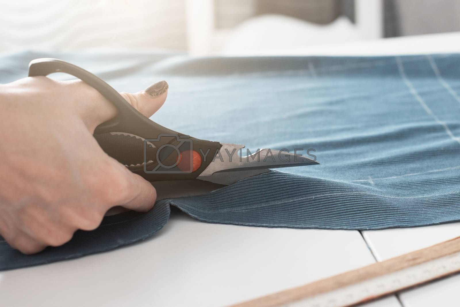 Woman dressmaker cutting fabric textile with scissors
