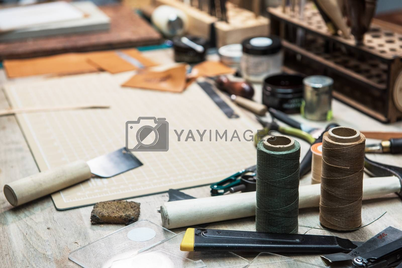 Leathermaker's work desk. Tools and leather at cobbler workplace. Tools for craft production of leather goods on wooden table.