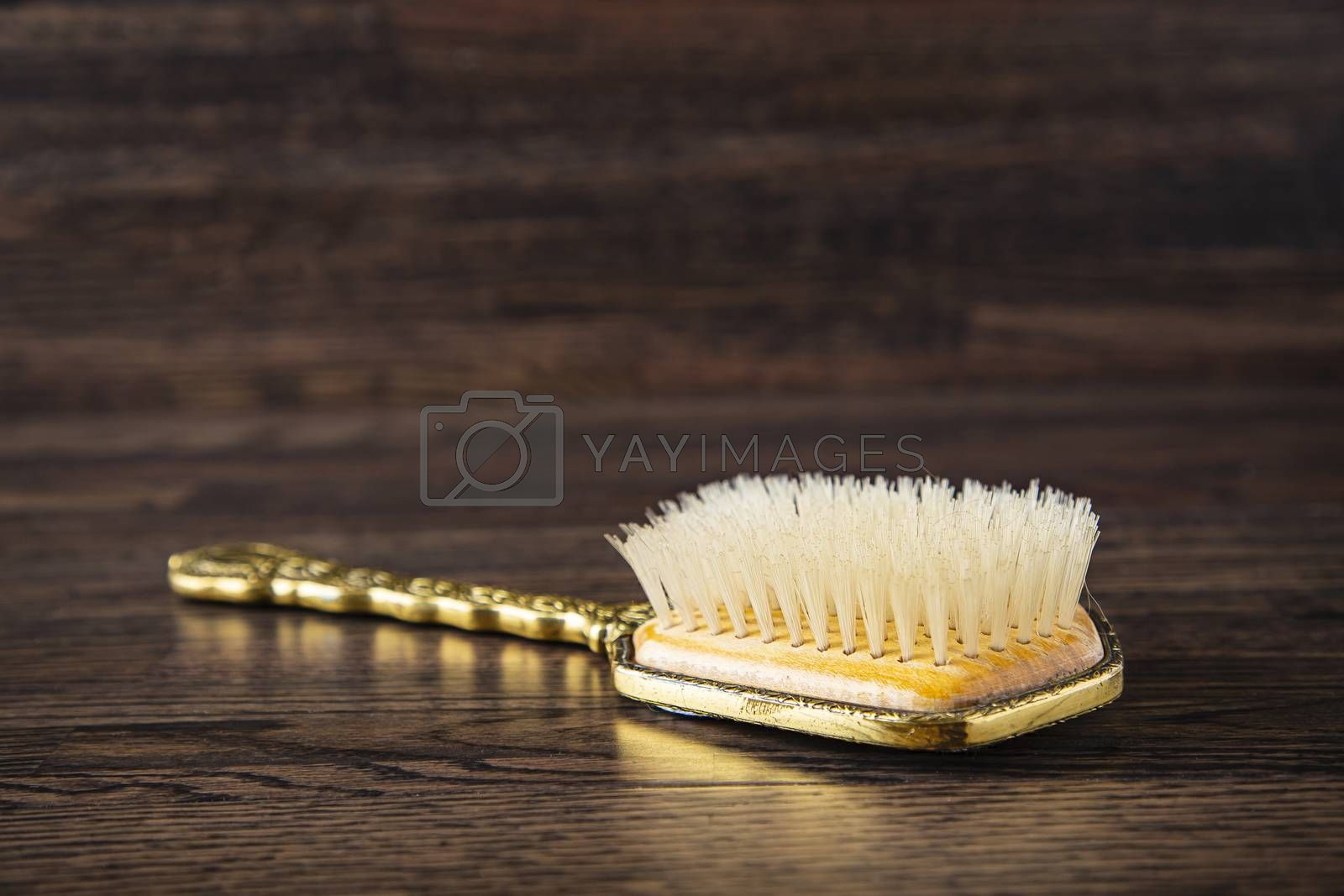 old vintage hair brush against a dark wood background