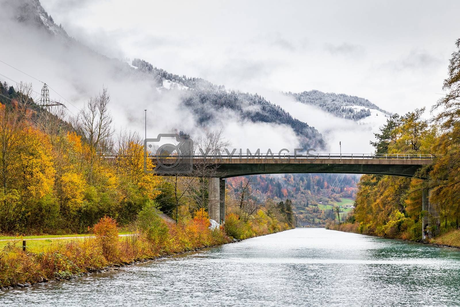 Road bridge across river to Thun lake, Interlaken, Switzerland. Early winter of November 2019, snow start to cover mountain area with cold temperature.
