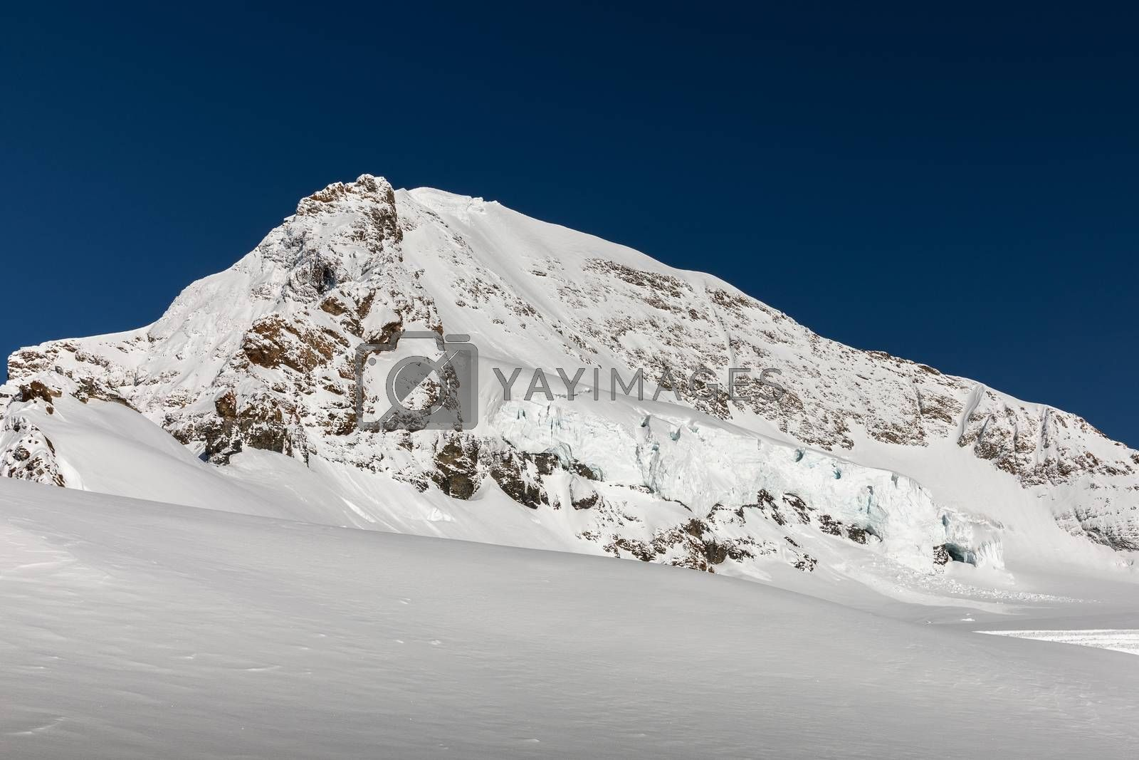 Rock peak of snow-capped mountain with blue sky in Jungfrau, Interlaken, Switzerland. Early winter of November 2019, snow start to cover mountain area with cold temperature.