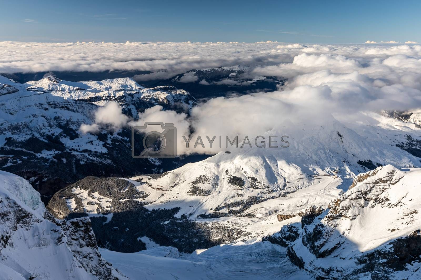Aerial of snowcapped mountain range of Jungfrau in winter before sunset on cloudy day, view from Jungfraujoch in middle of Jungfrau and Monch, Interlaken, Switzerland.