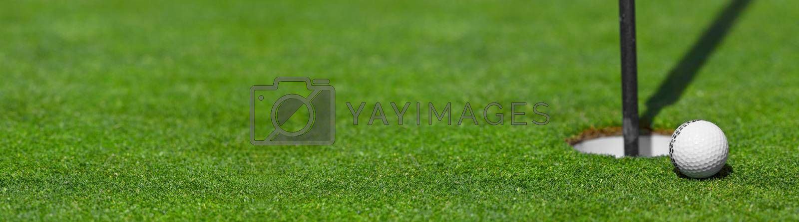golf ball on lip of cup course background with copy space