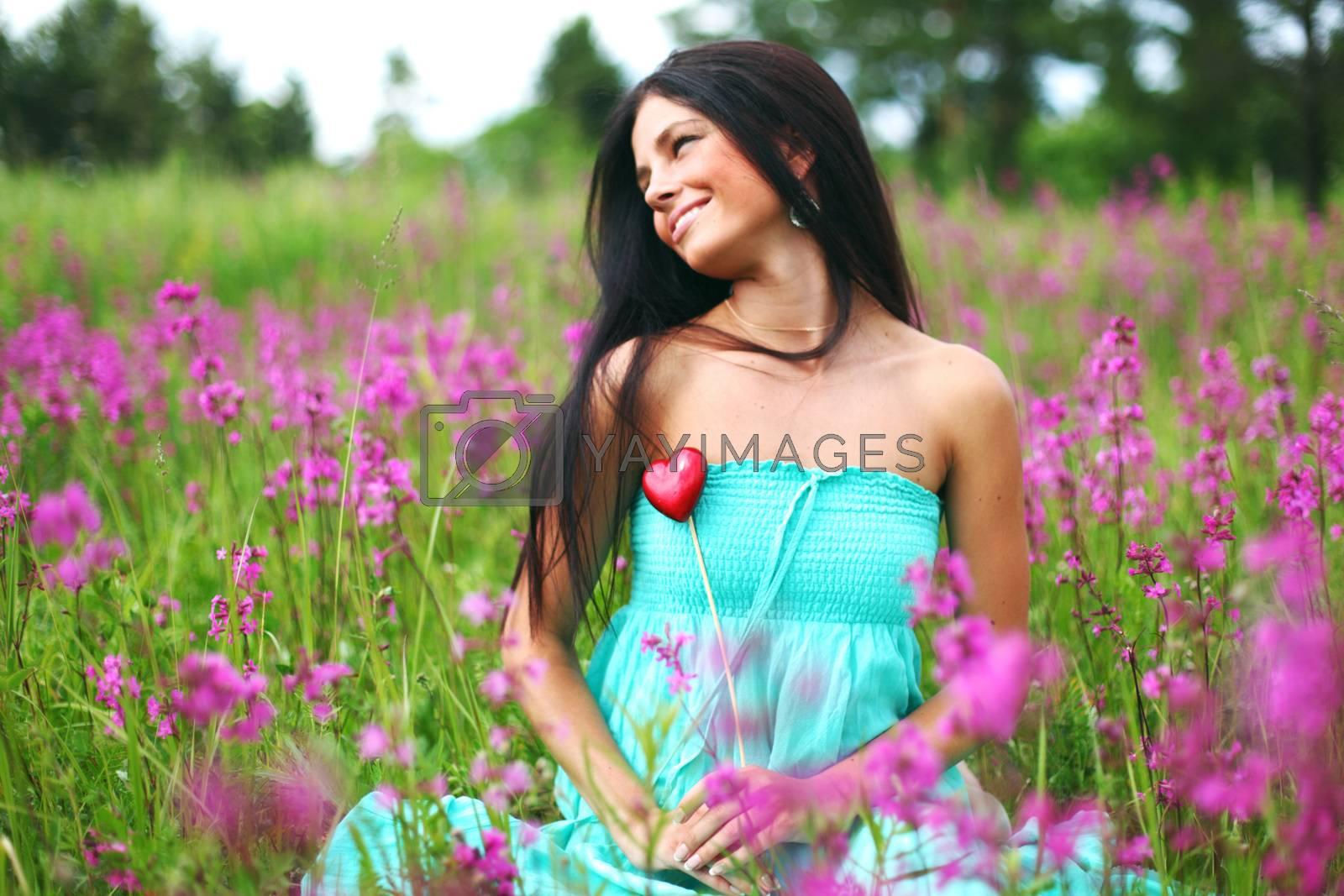 woman on summer flower field meadow heart in hands love nature