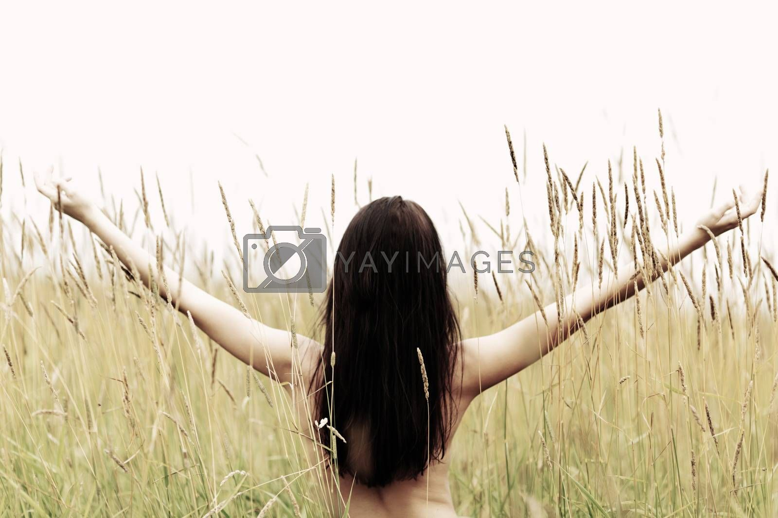 woman on grass field feel freedom standing with arms raised