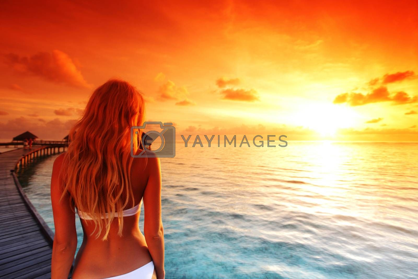 woman in bikini on a bridge home sea and the maldivian sunset on the background
