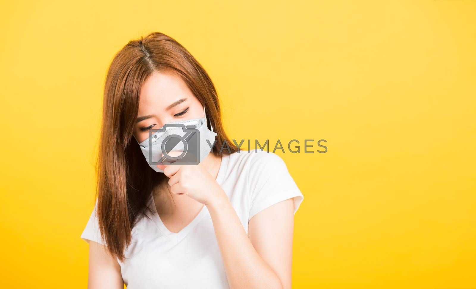 Asian happy portrait beautiful cute young woman teen standing wear t-shirt cough in mask protection from virus epidemic or air pollution isolated, studio shot on yellow background with copy space