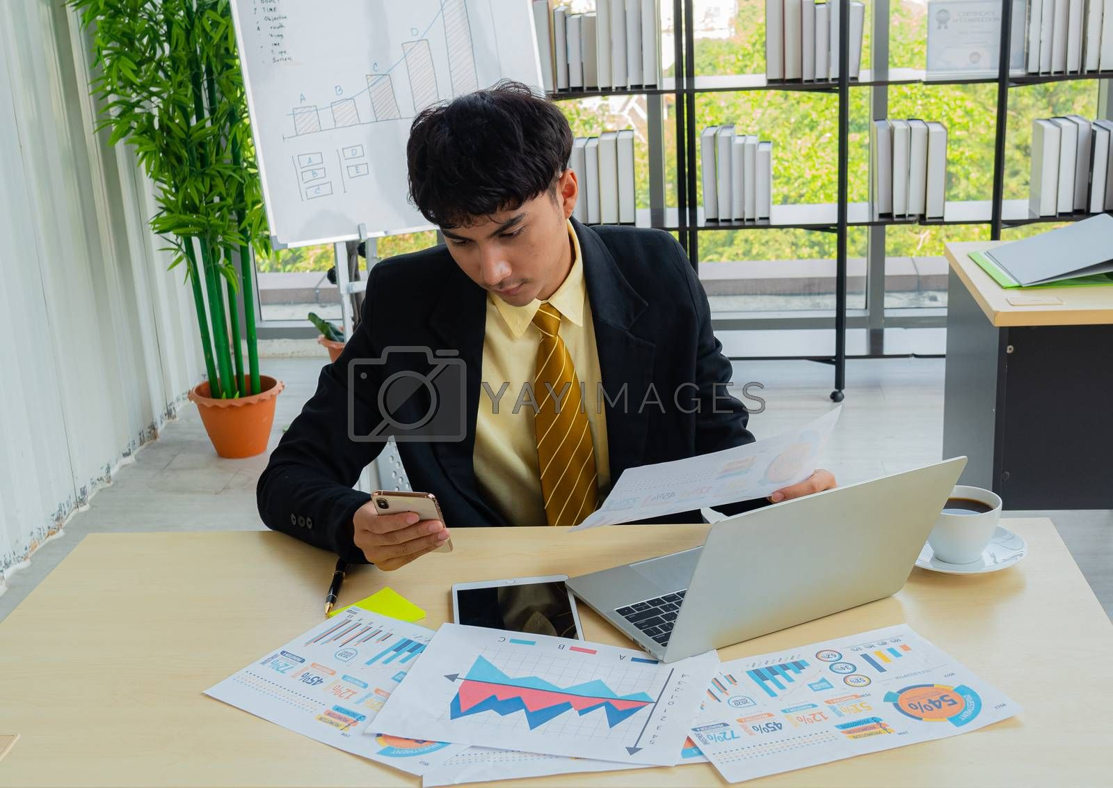 Young business people are concentrating on their work by comparing the results of their mobile phones with hand-held documents on the office desk full of information in the modern office.