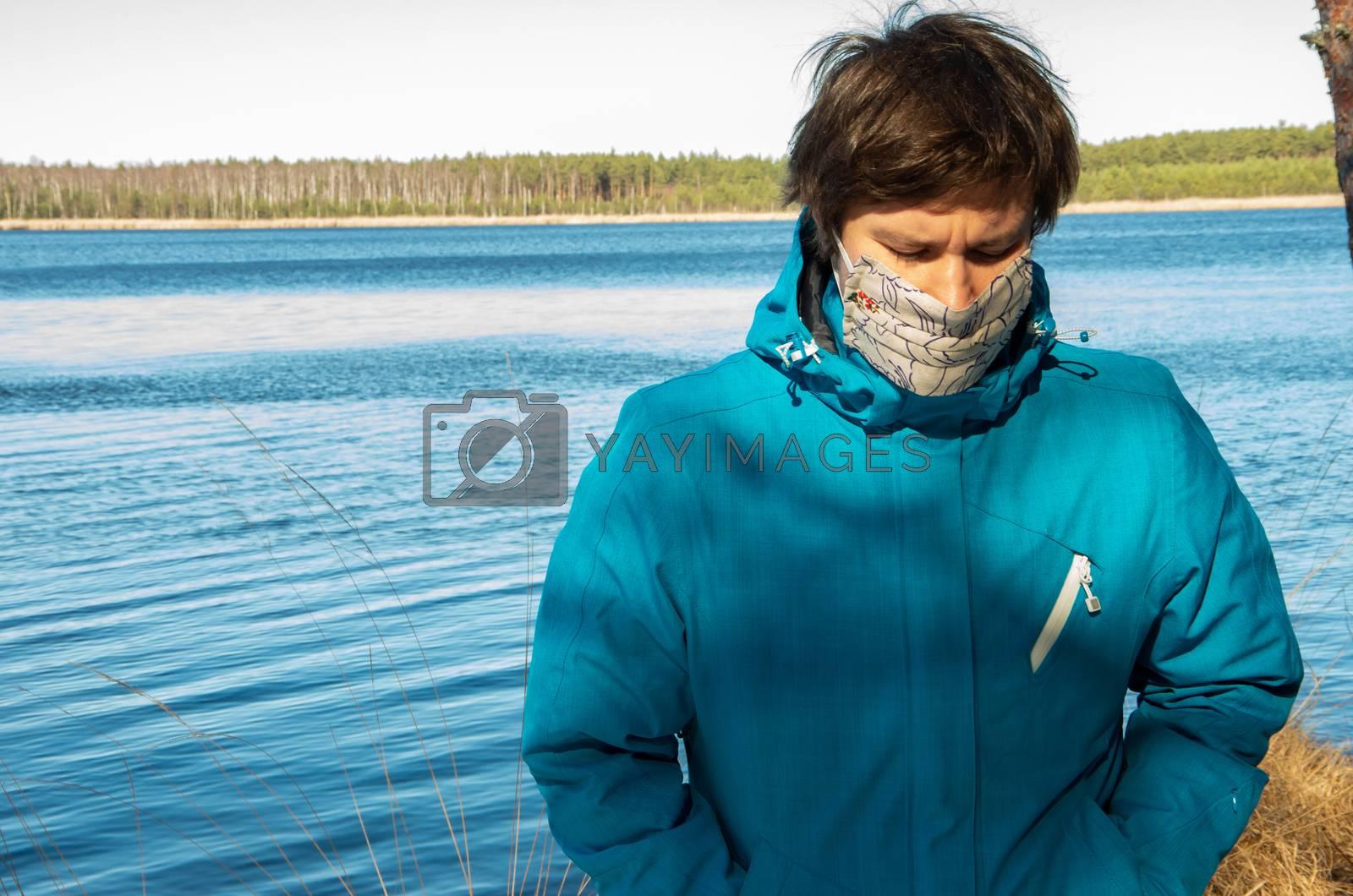 Virus, man with white face mask in a blue jacket, coronavirus, COVID-19, lake