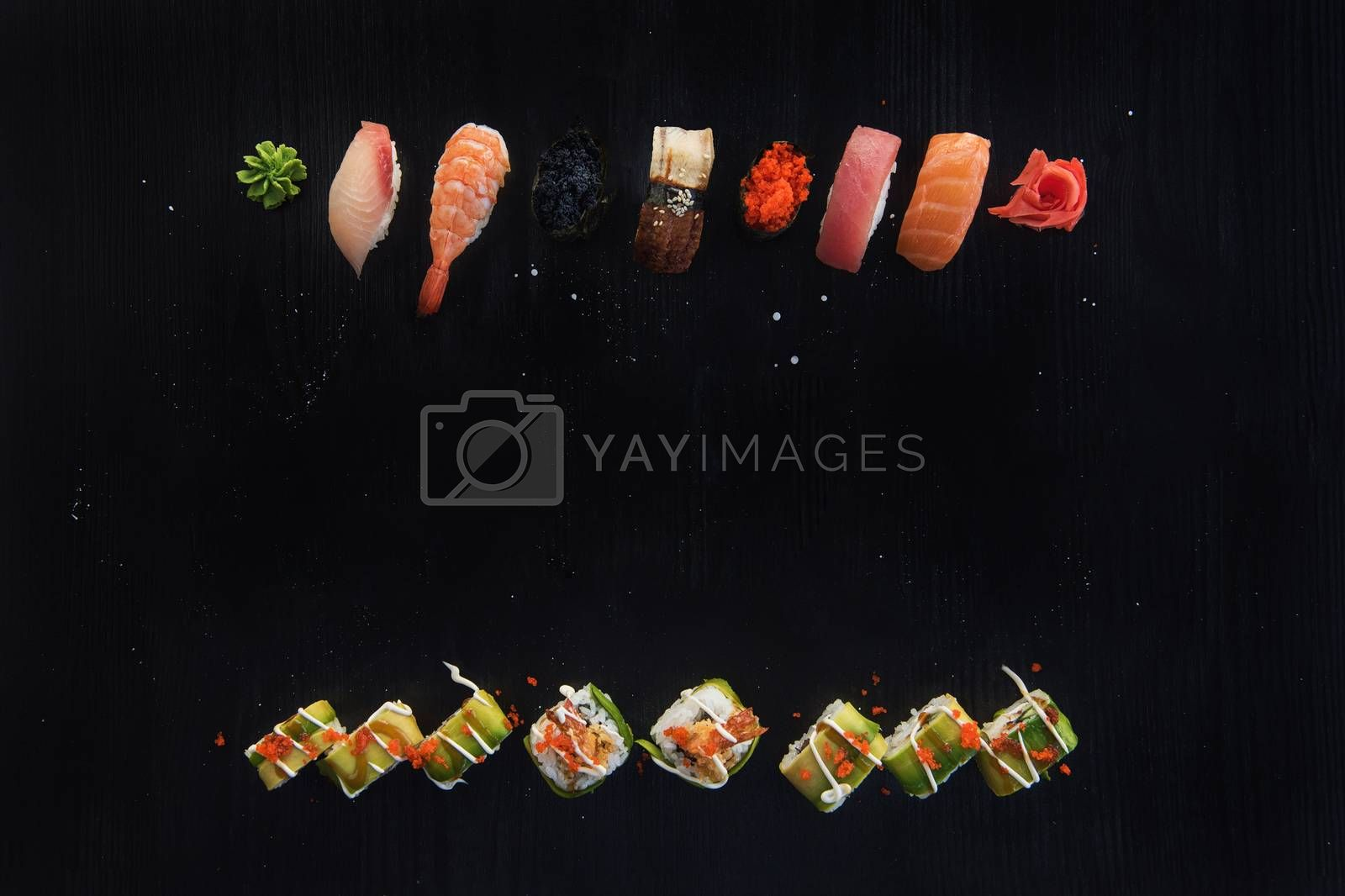 Various kinds of sushi served on wood black table. Concept of sushi menu for Japanese food