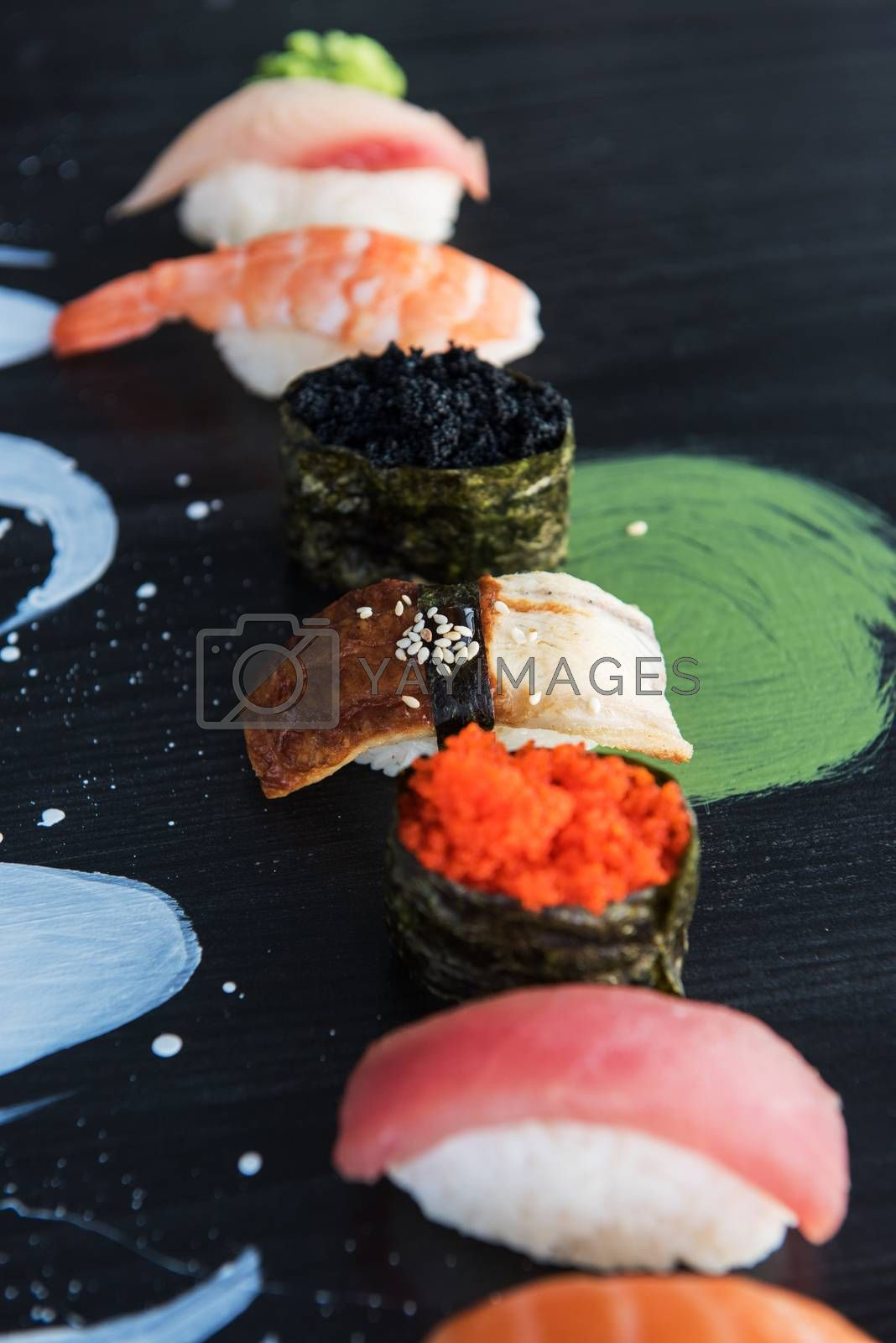 Various kinds of sushi served on wood black table.