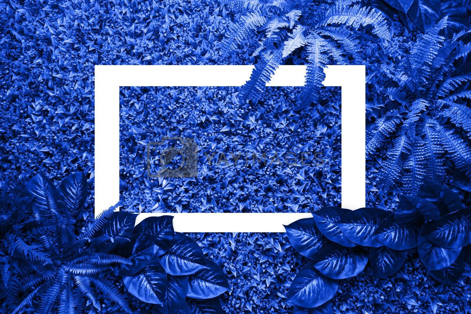 Classic blue color background from leaves and white frame for your design. Pantone color of the year 2020.