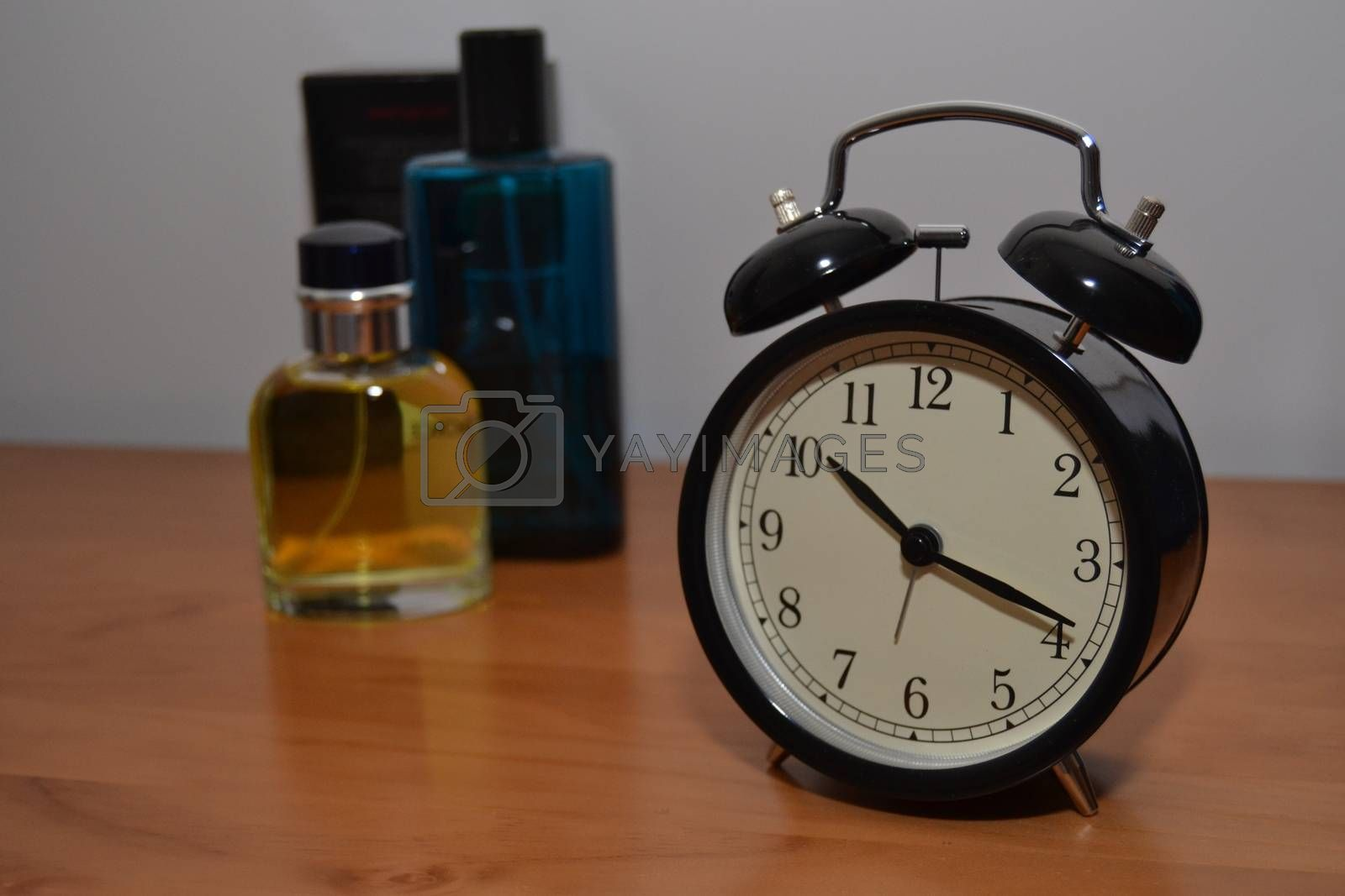 Glamorous scene with a perfume bottle background and an antique alarm clock black and white