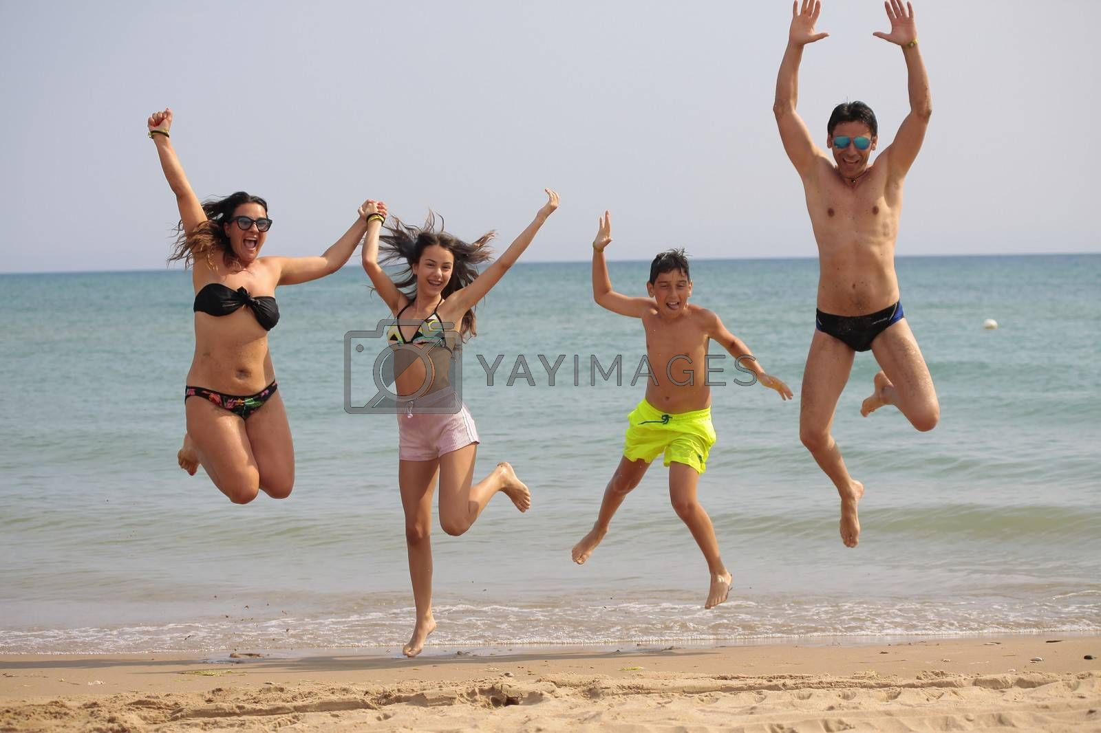 Jumping family with four people posing in seaside
