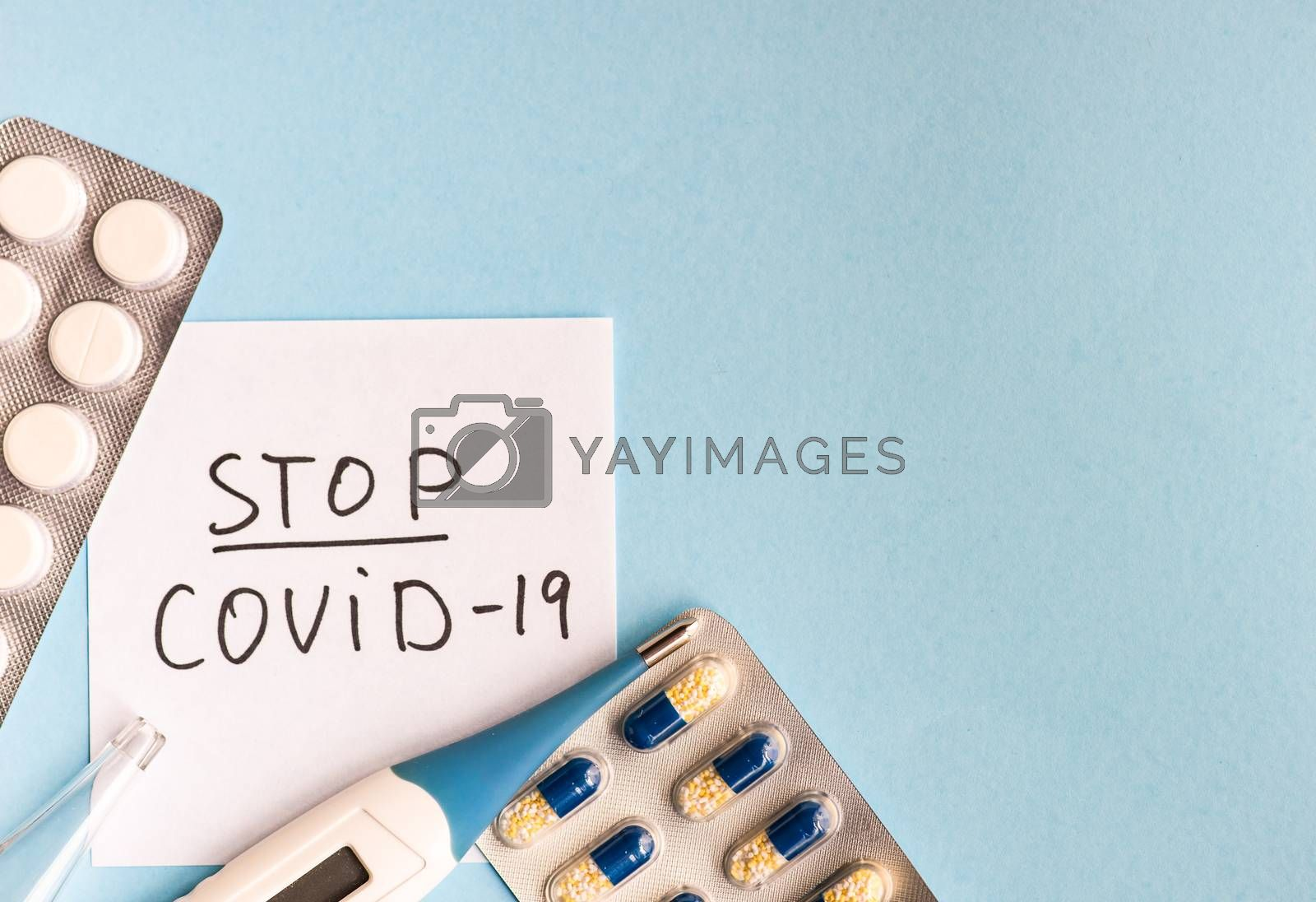 COVID-19 virus concept with pills and other safe staff  on pastel background with copy space