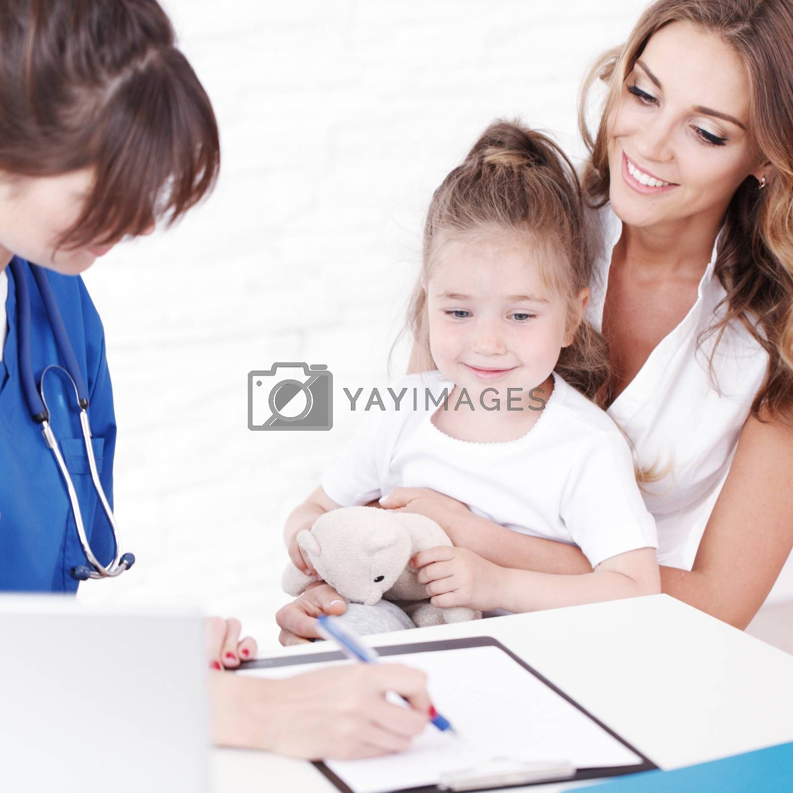 Pediatrician doctor writing prescription to girl and her mother