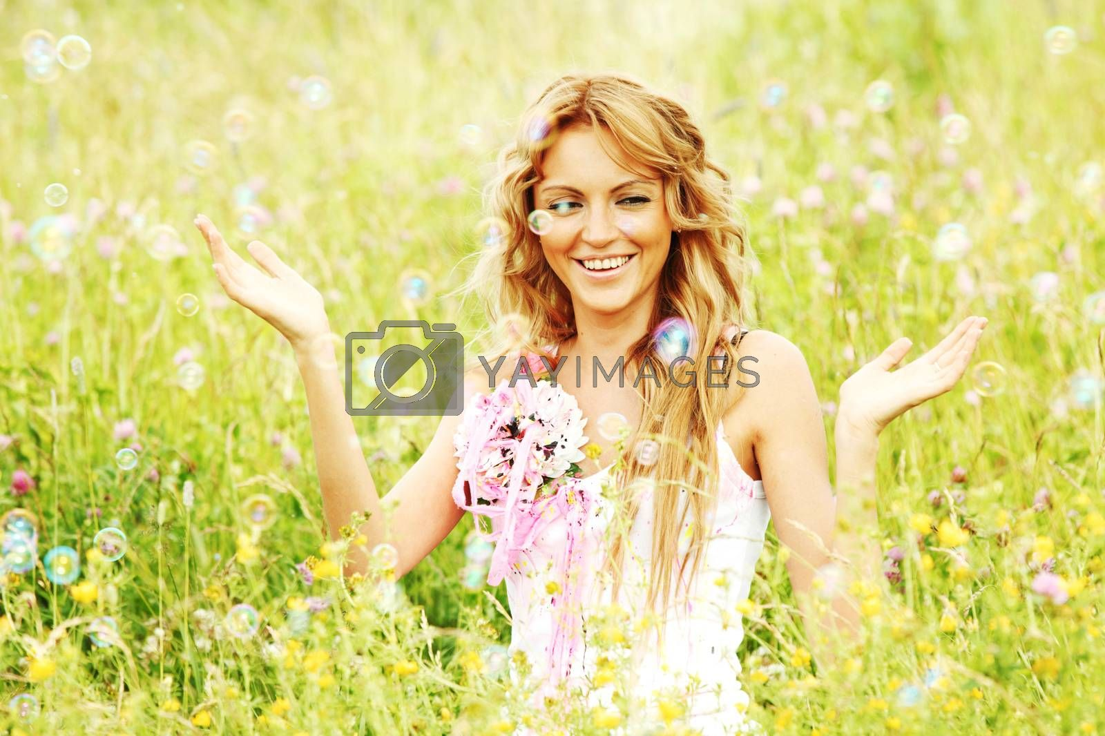 Blonde girl starts soap bubbles and smiling in a green spring field