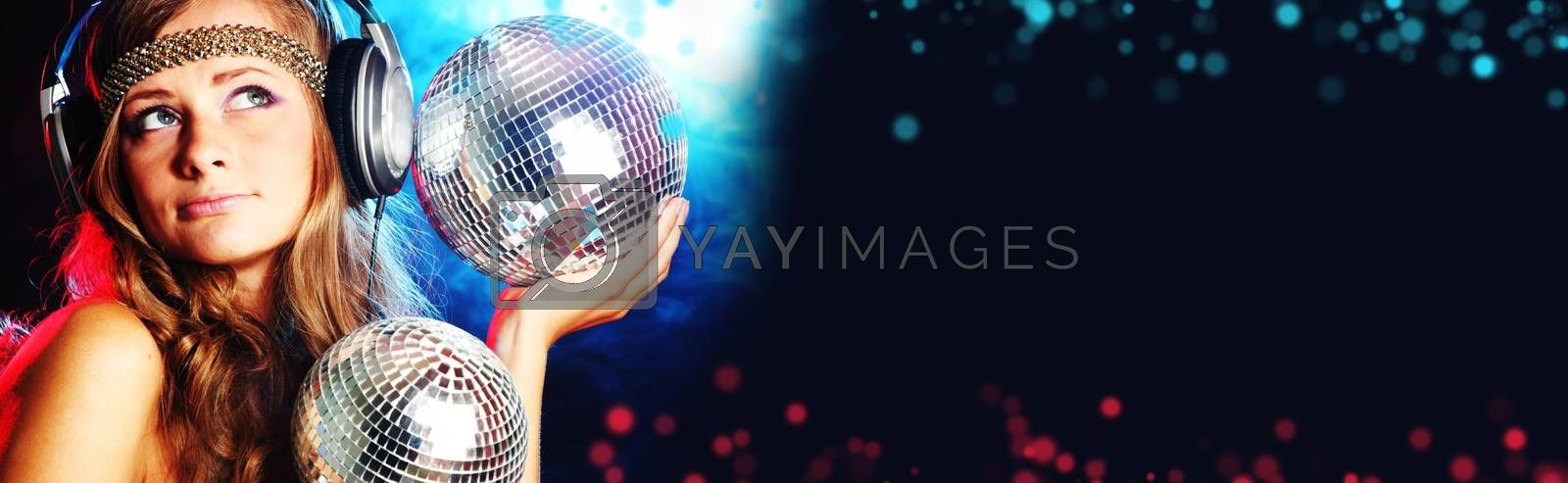 Disco girl enjoys music in head phones holding mirror disco ball over black and colorful bokeh background