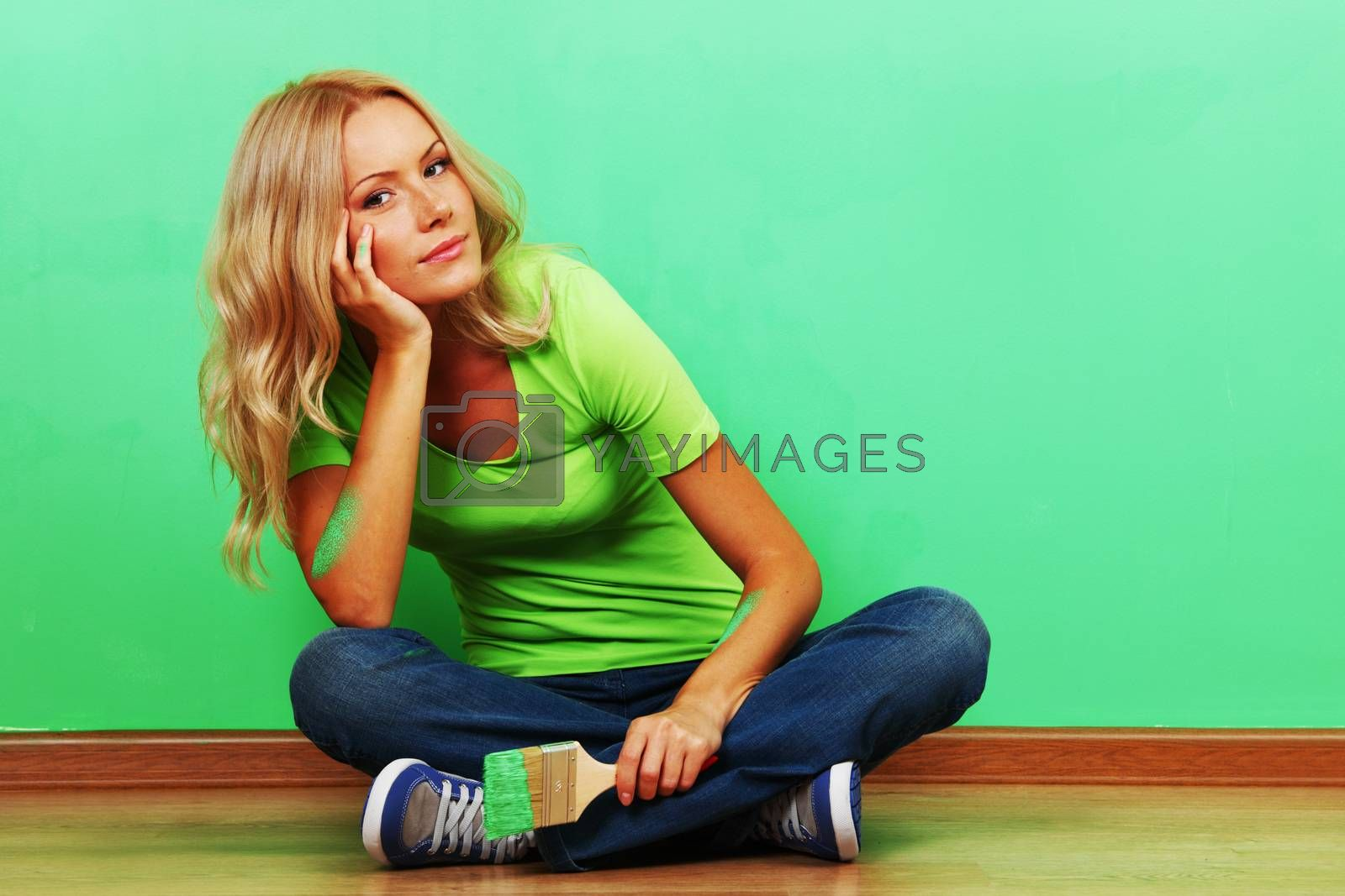 Young attractive woman sitting and smiling looking at fresh painted wall finished renovation holding pint brush, copy space for text