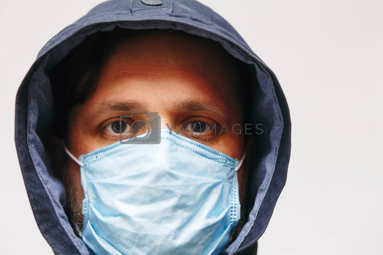 Man in hood with mask to protect him from Coronavirus. Corona virus pandemic. Young man with medical mask isolated. Person in hood with medical mask. COVID by Denys_N