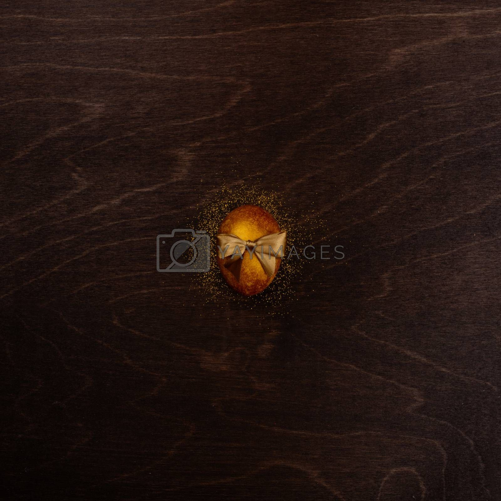 One big golden easter egg with ribbon bow on dark wooden background copy space for text