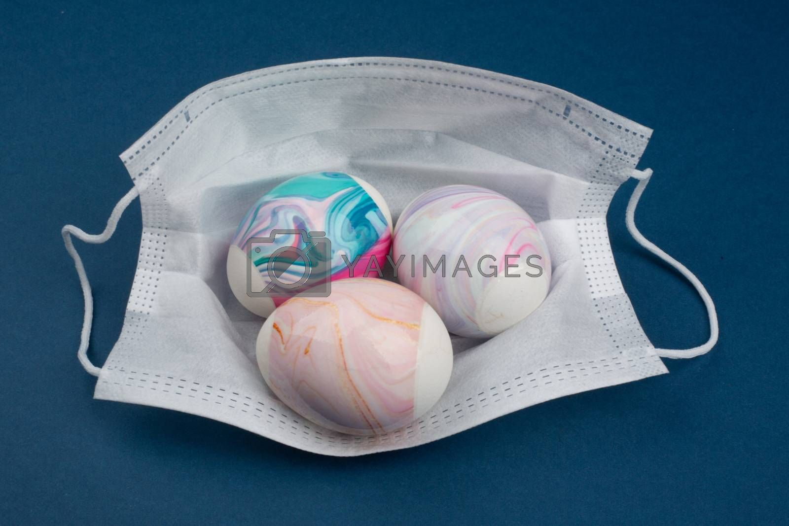 Easter 2020 conceptual image with color easter egg in protective medical mask. Cancellation of celebration concept coronavirus pandemic. Antiviral mask. COVID quarantine. Protection from virus COVID-19