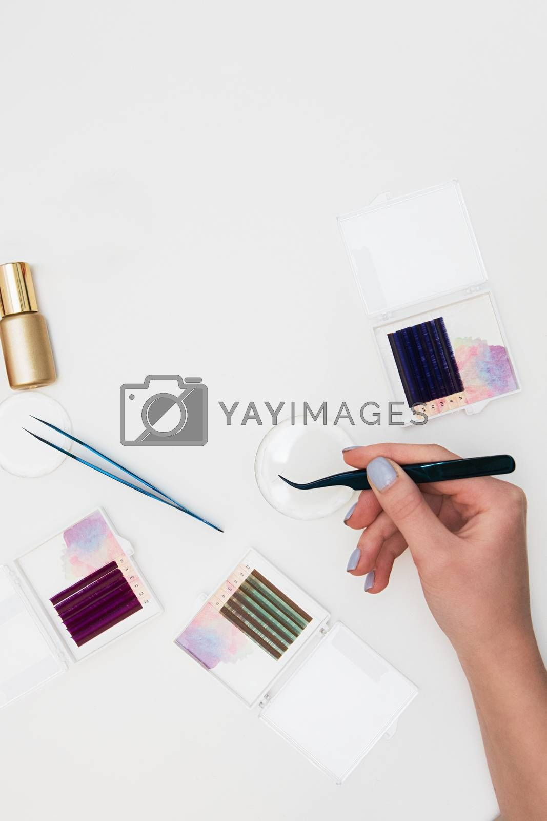 Tools for eyelash extension procedure. Hand with tweezers with artificial black lashes on gray background. Beauty concept