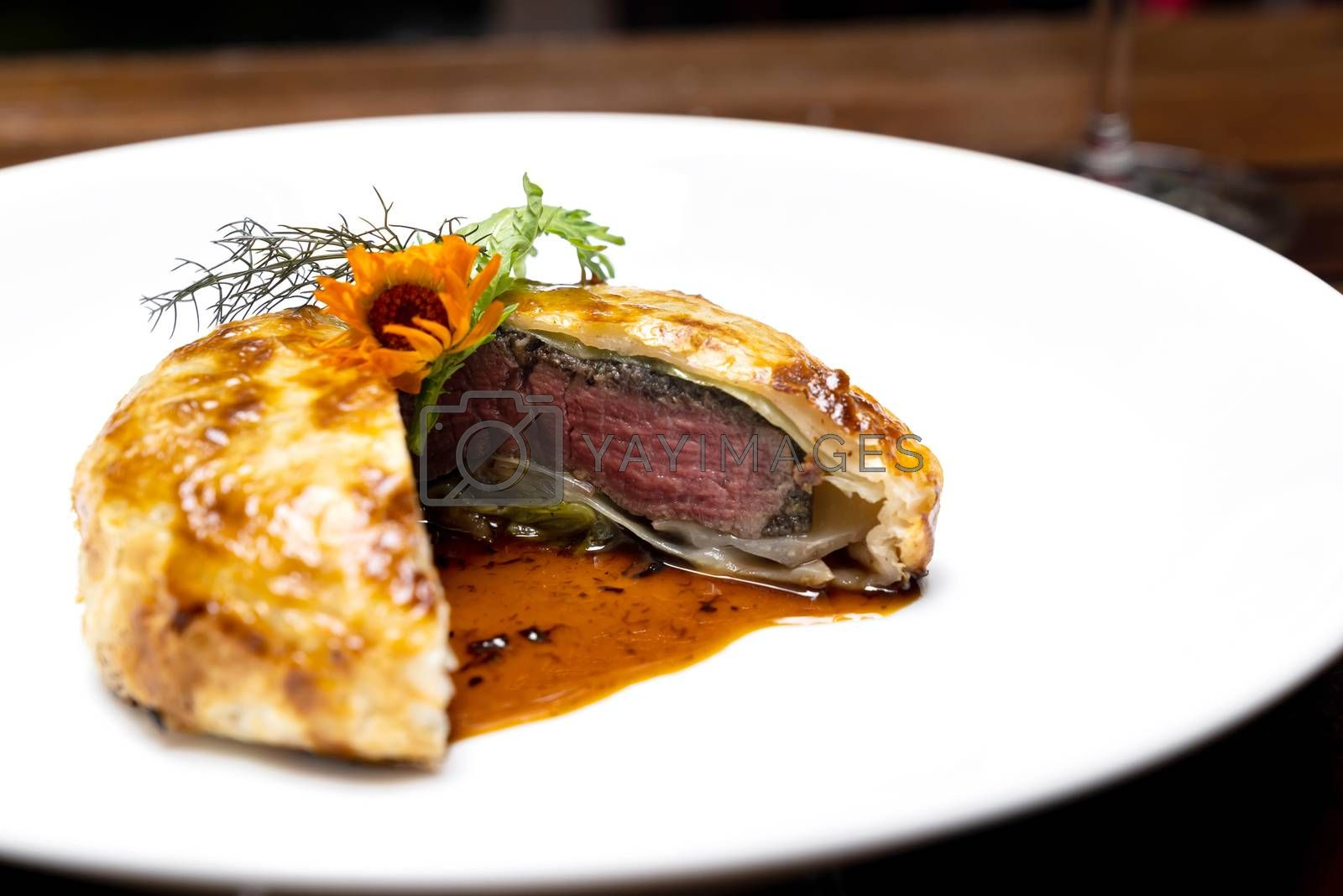 Roasted Beef Wellington with gravy brown savory sauce, international gourmet cuisine of stuff beef meat in baked bread puff. Unising for recipe menu pf food and drink industry.