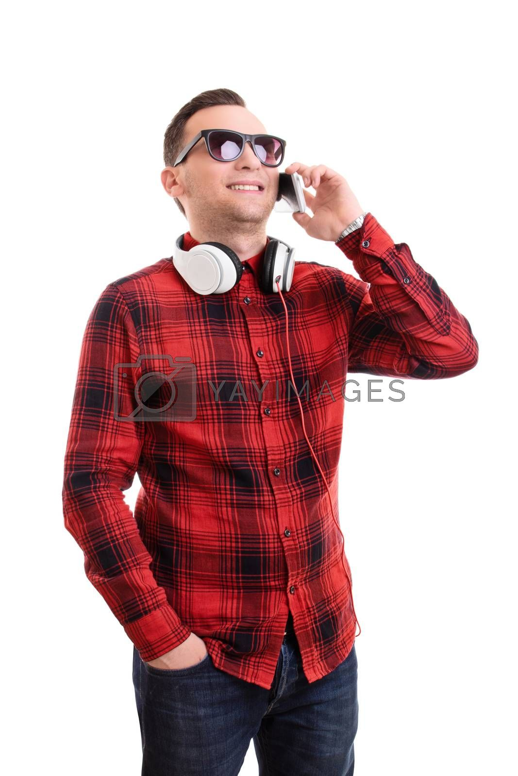 Communication and technology concept. Portrait of a handsome smiling young man in plaid shirt talking on his mobile phone and wearing headphones around his neck, isolated on a white background.