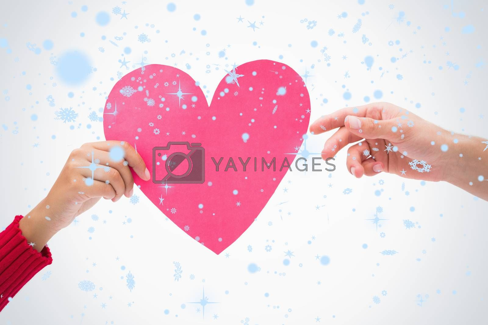 Composite image of Woman passing man pink heart with snow falling
