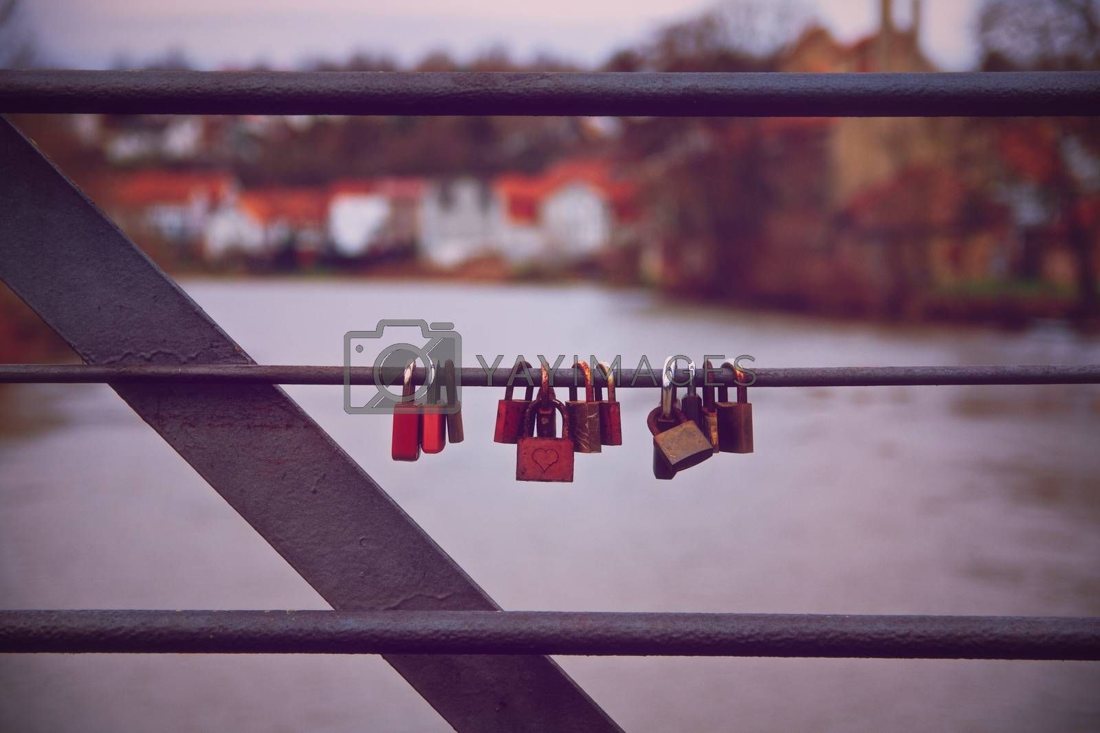 Lovelocks hanging on a bridge railing with a river in the background. Romantic lover padlocks on a bridge in a symmetric row. Symbol of unbreakable love and lifetime commitment for couples. Love, marriage, relationship concept.
