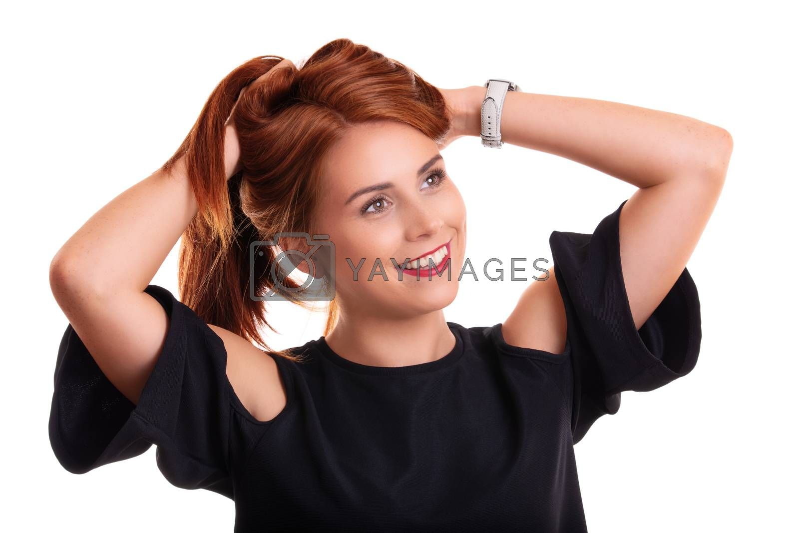 Portrait of a beautiful smiling young redhead woman with hands in her hair, isolated on white background.