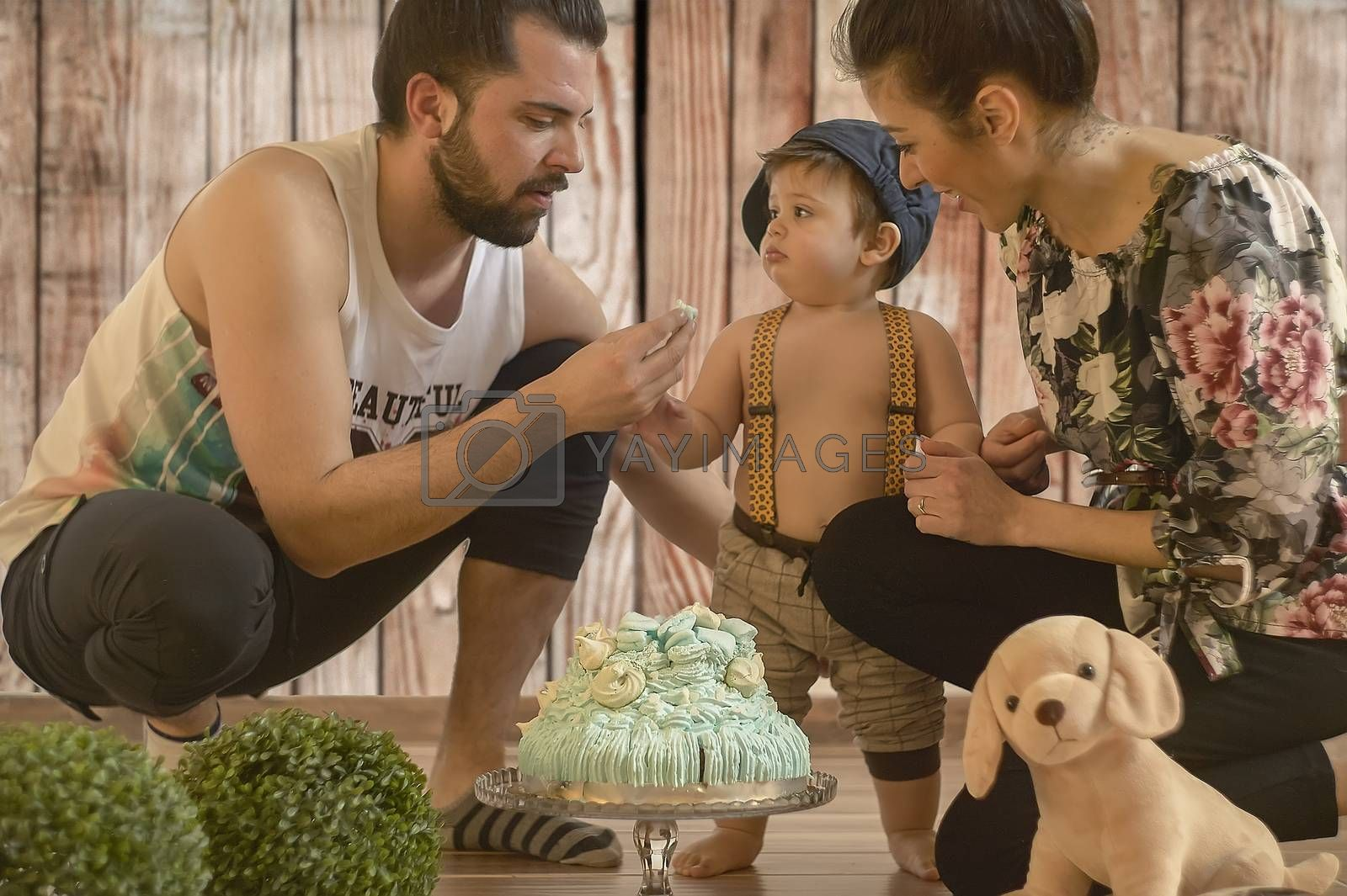 Baby with birthday cake in a photographic set with mom and dad