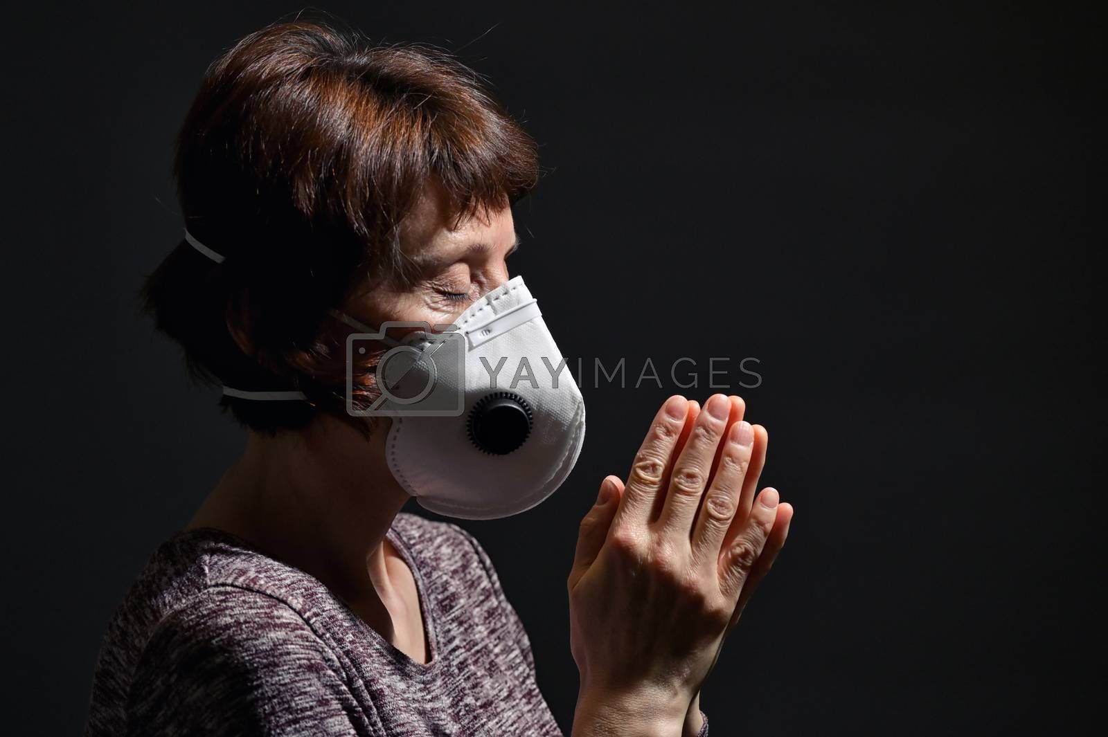 Woman Wearing Medical Protective Virus Mask and pray on dark background