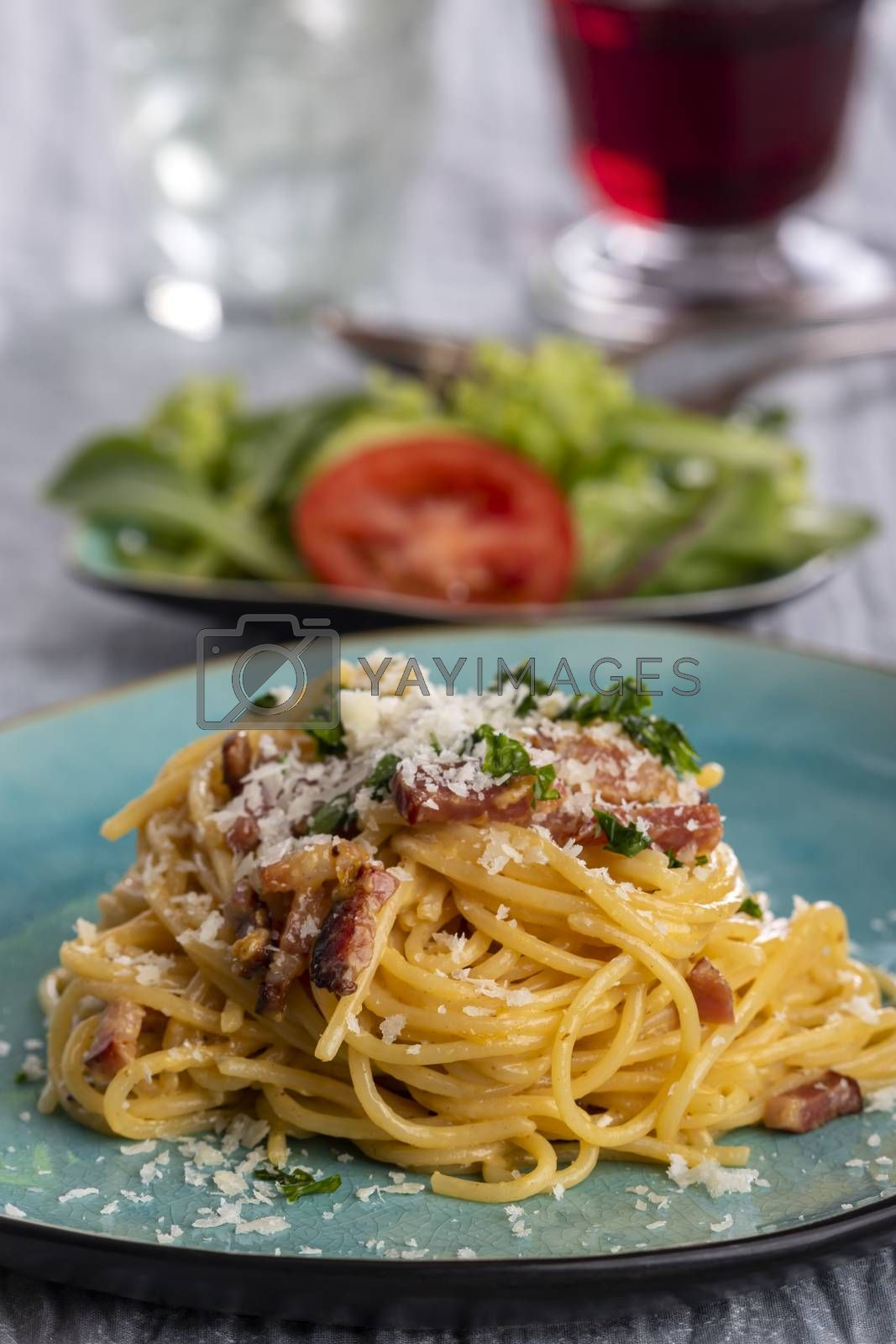 spaghetti carbonara on a blue plate by bernjuer