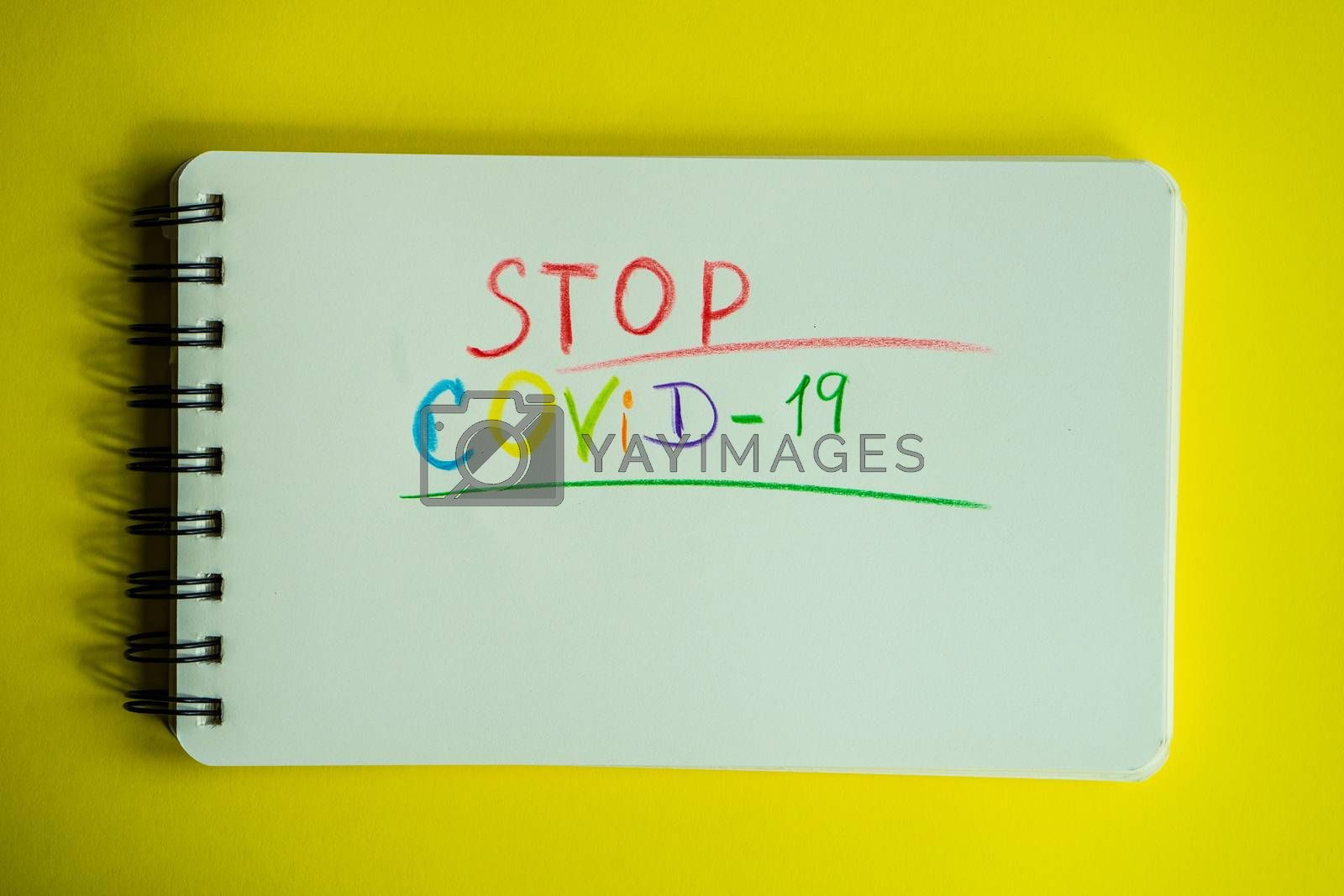 COVID-19 virus concept with note on pastel yellow background with copy space