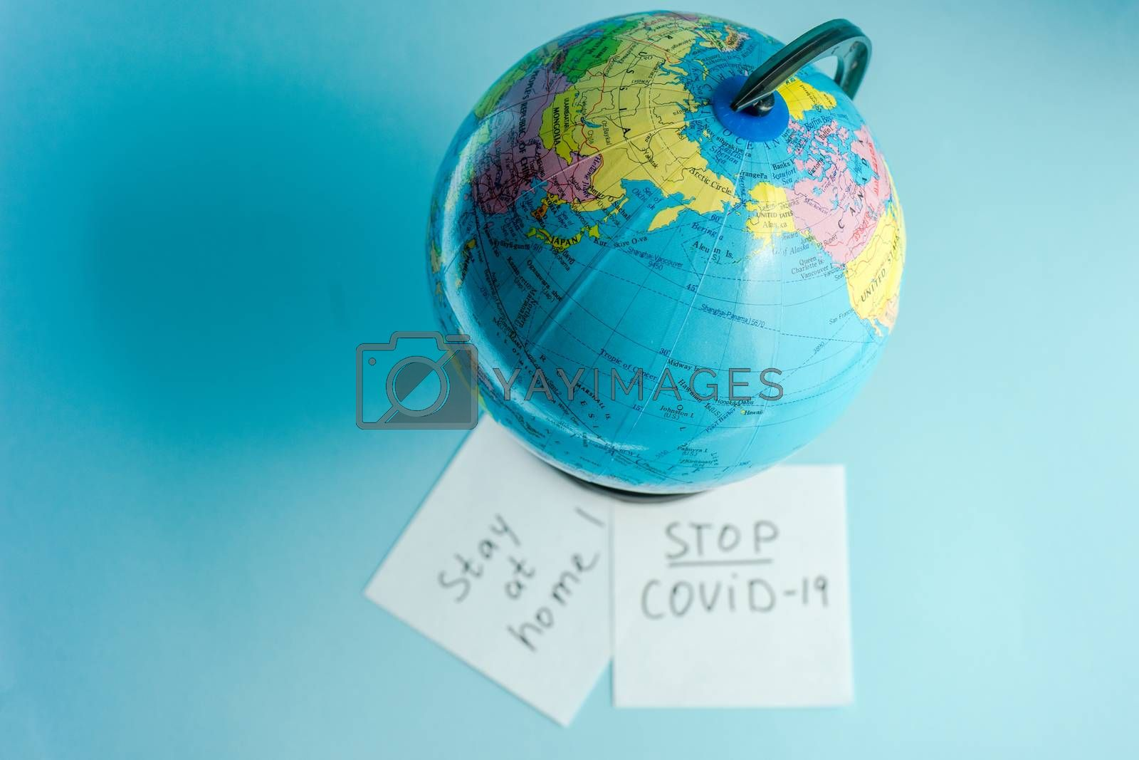 COVID-19 virus concept with Earth globe in face mask on pastel background with note and copy space